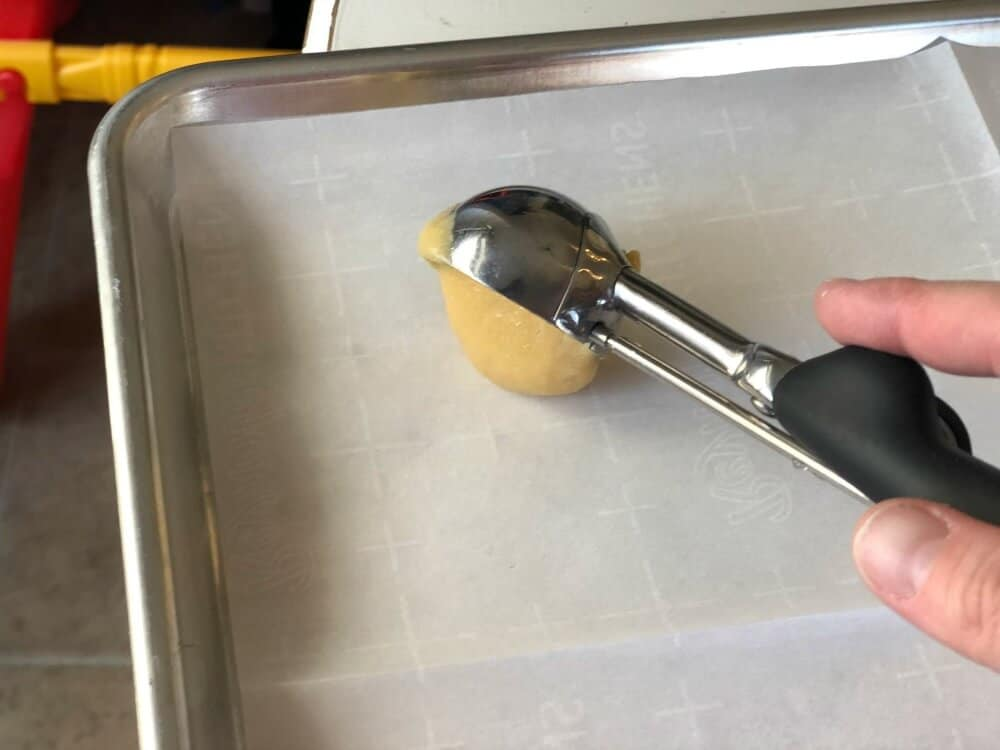 one ounce scoop dropping cookie dough onto a parchment lined backing sheet