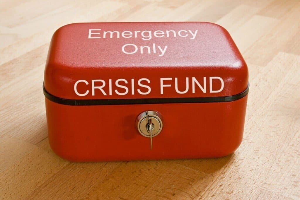 Red lockbox that you could keep money in that says Emergency Crisis Fund across the top