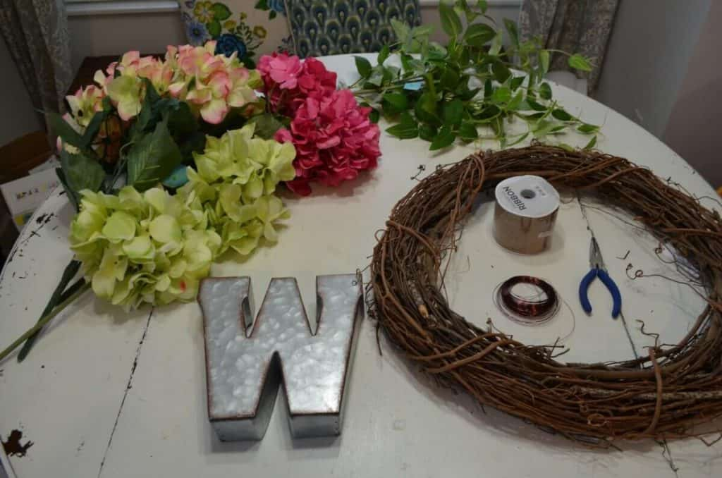 Supplies to make grapevine spring wreath, including flowers, greenery, burlap ribbon and monogram letter