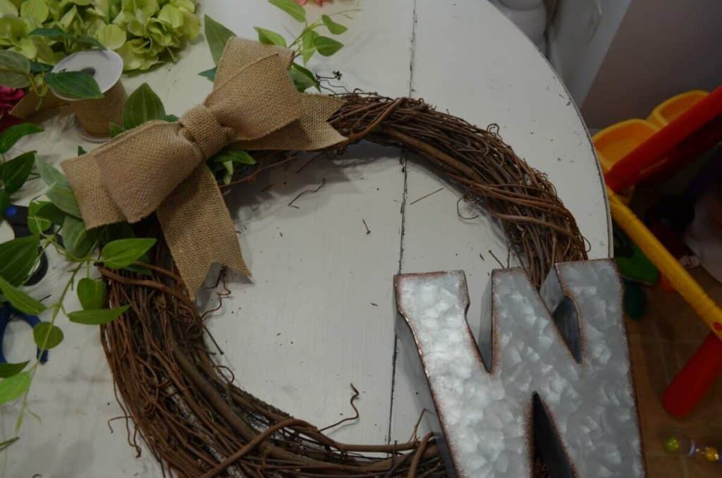 Beginning assembly of a grapevine wreath with bow and monogram letter