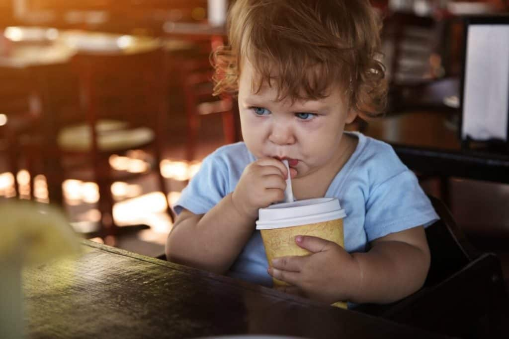 Sad, pouting toddler sitting at a table in restraunt drinking out of a cup with a straw.