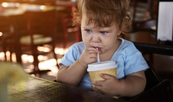 Sad toddler sipping out of a cup with straw at restaurant