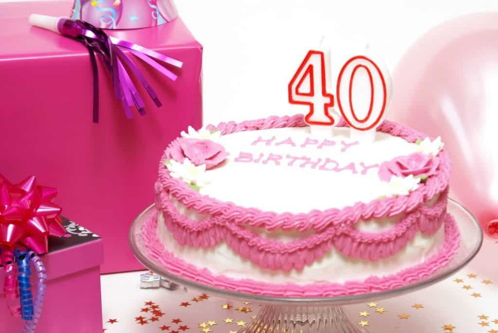 "Table with white tablecloth and convetti, with pink wrapped presents and party hats and a pink and white birthday cake with ""40"" candles on top"