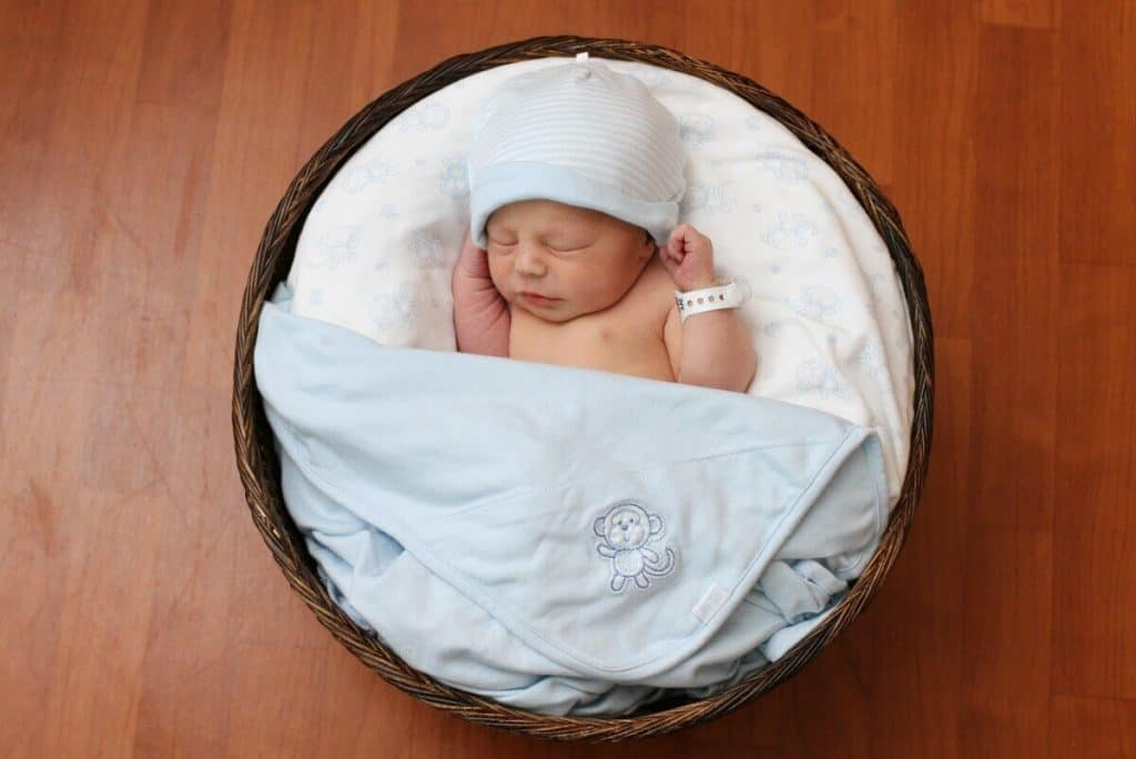 Newborn baby in a basket with a blue hat and blue blankets
