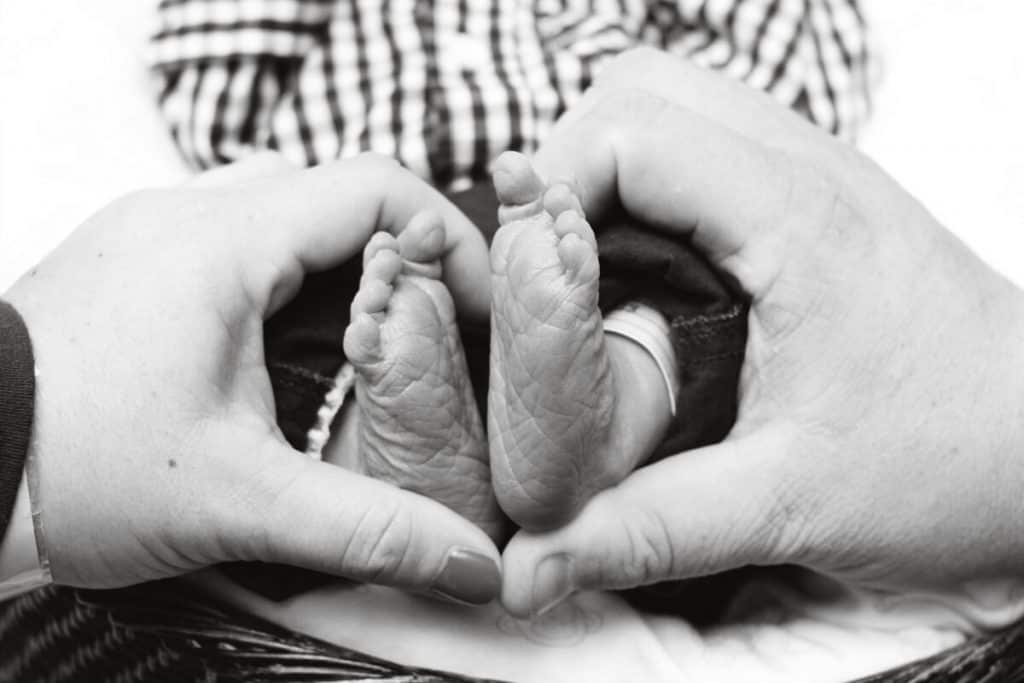 black and white picture of baby's feet with parents holding the feet