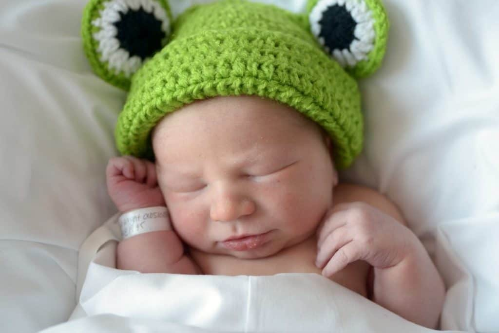 Newborn baby in a basket with white blankets and a green frog hat