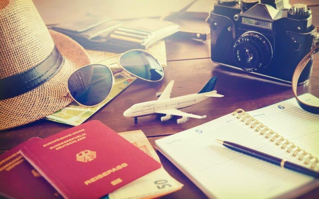 Vacation items on a table including passport, money, journal, camera, sunglasses, wallet and straw hat