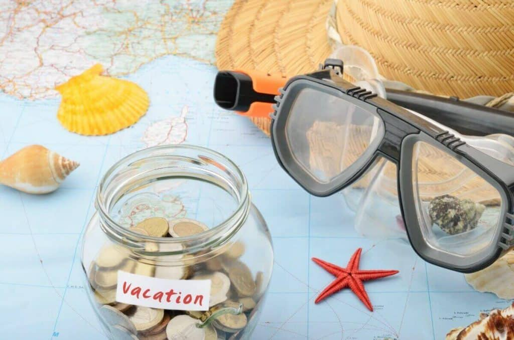 Vacation change savings jar with snorkel gear, a straw hat and a map with a few seashell scattered about