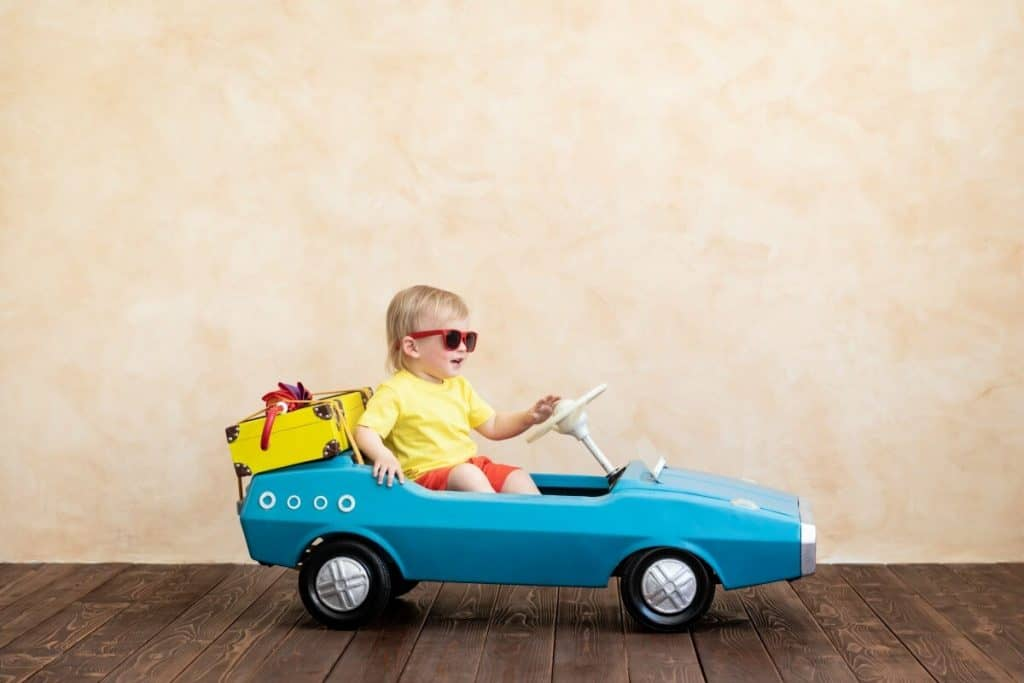 toddler with sungalsses driving a small pedal car with suitcase and umbrella strapped to the back