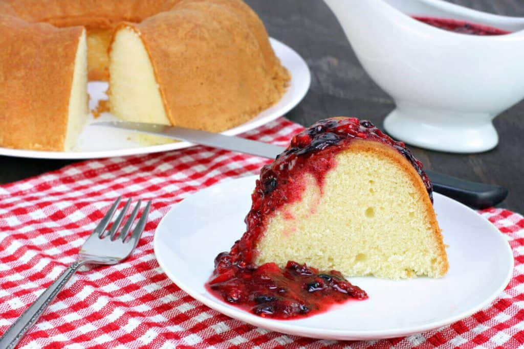Lemon Pound Cake with Berry topping on white plate and red and white napkin