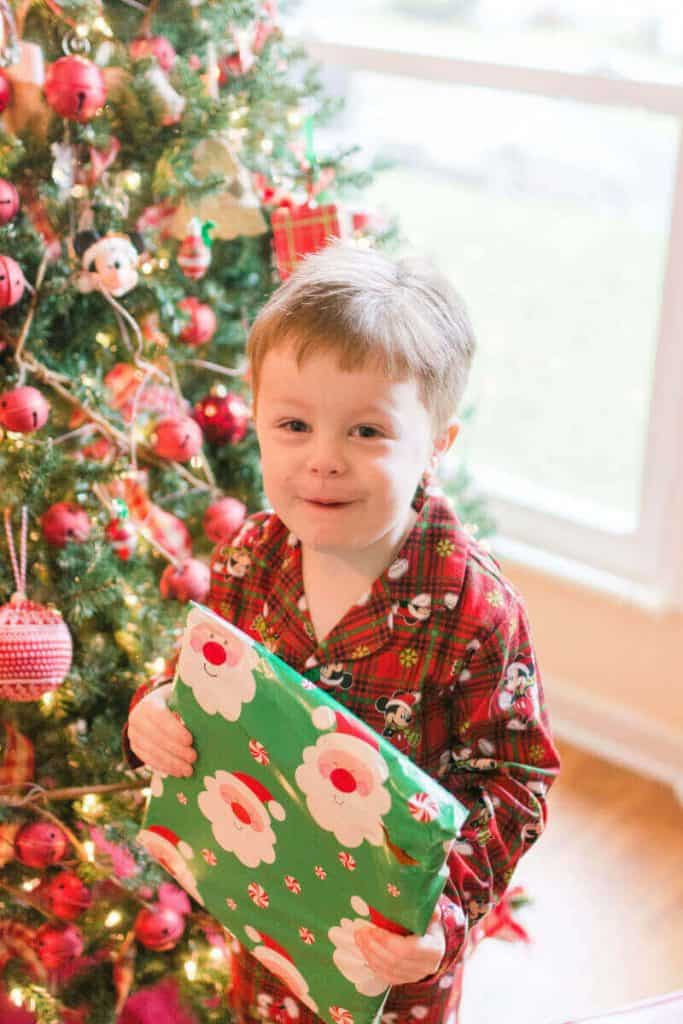 Boy in front of christmas tree holding a package