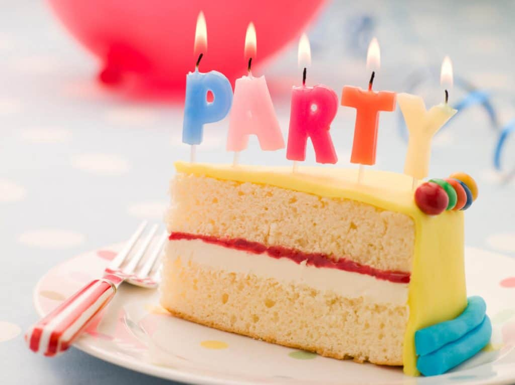 Colorfully iced birthday cake on white plate with party candles lit up