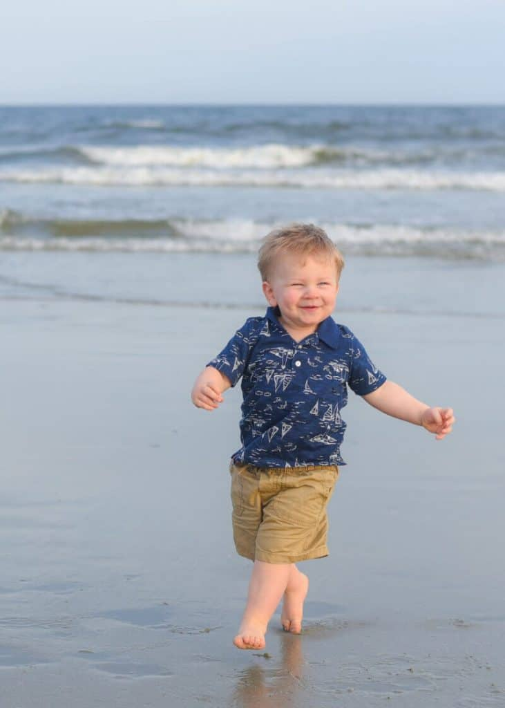 Toddler smiling and running on the beach