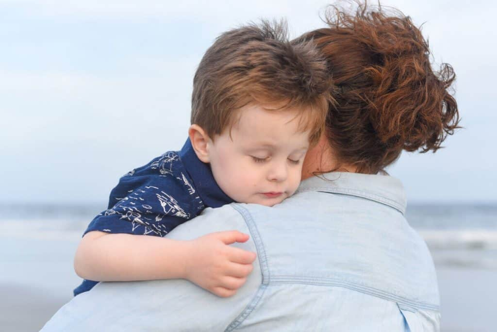 Toddler sleeping on his mom's shoulder on the beach
