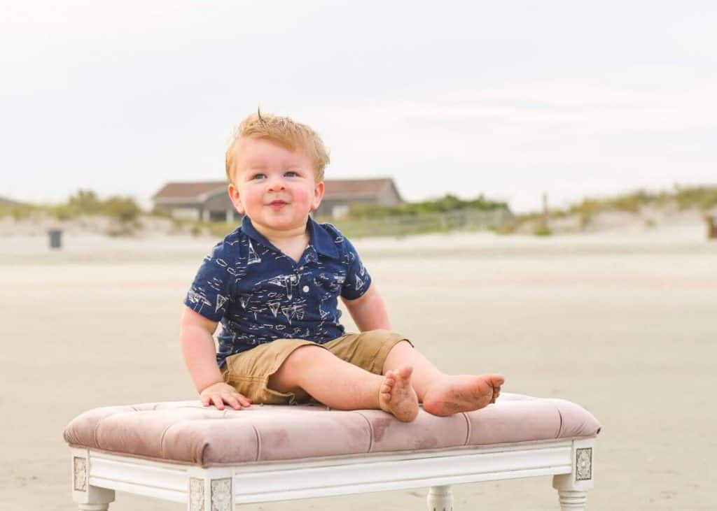 Toddler on a bench on the beach smiling