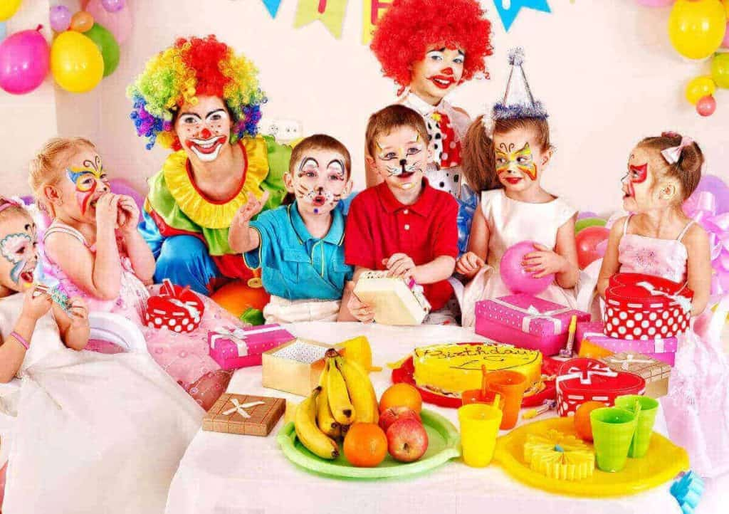 Child's birthdy party with kids around a table with faces painted and a clown with cake and gifts and snacks