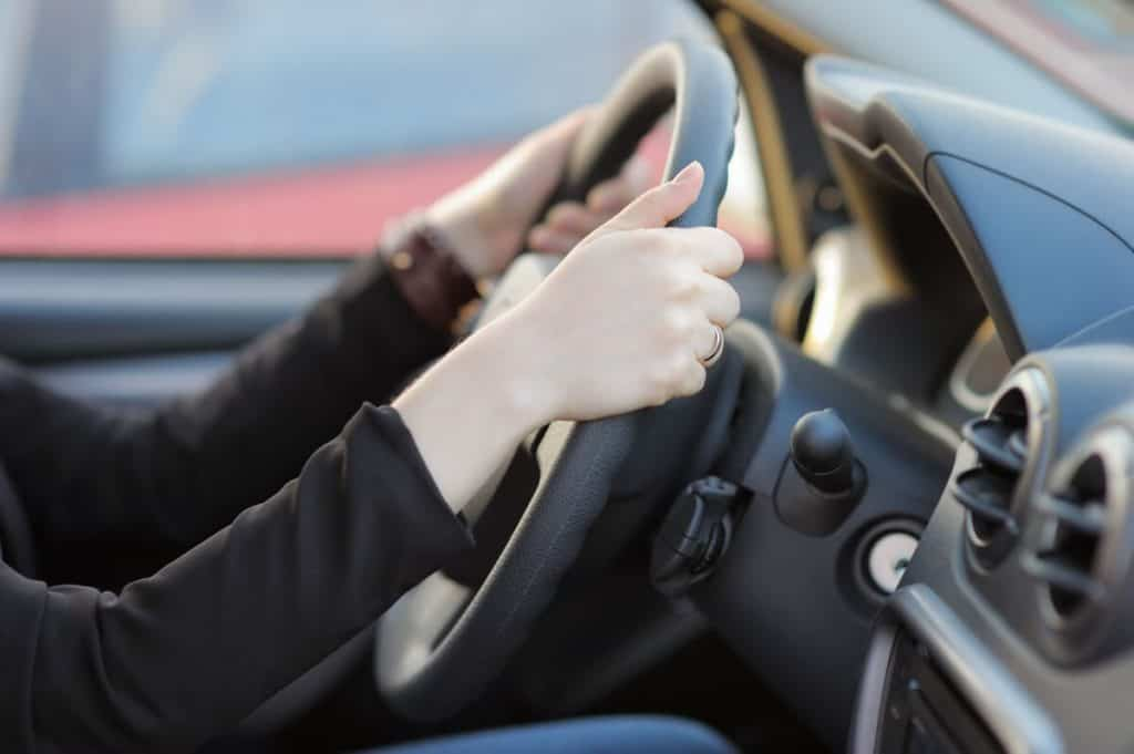 woman gripping steering wheel while driving in car