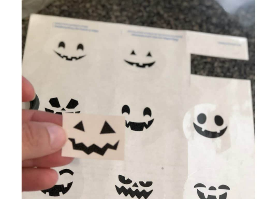 Black jack-o-lantern faces printed onto a sheet of clear round labels