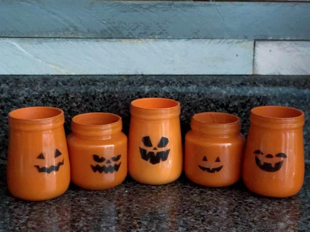 5 jack-o-lantern painted babyfood jars lined up