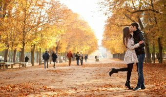 Couple kissing in a park along a path with fall changing leaves all around them