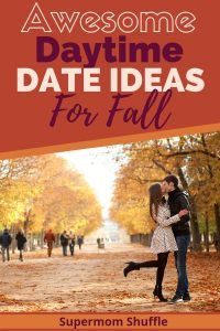 Couple kissing in the park with fall leaves on the ground and brightly colored trees