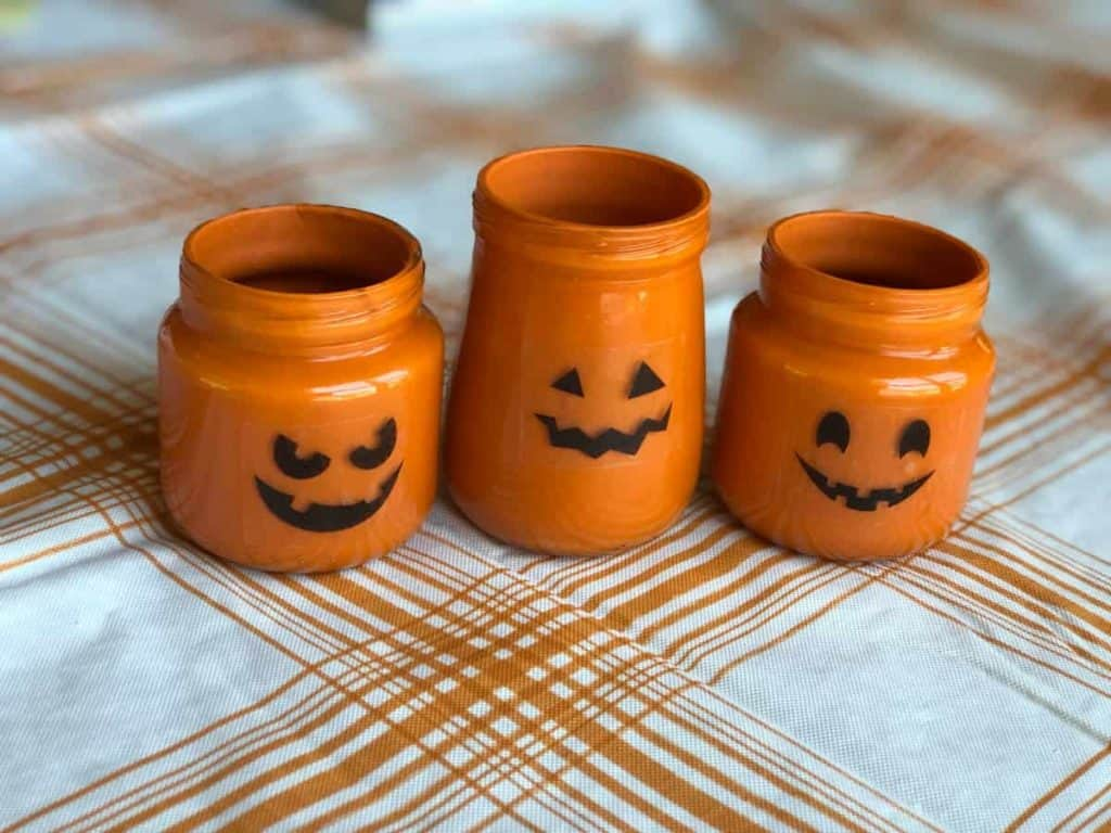 Baby food jars painted orange with Jack-O-Lantern faces on them sitting on a white and orange plaid tablecloth