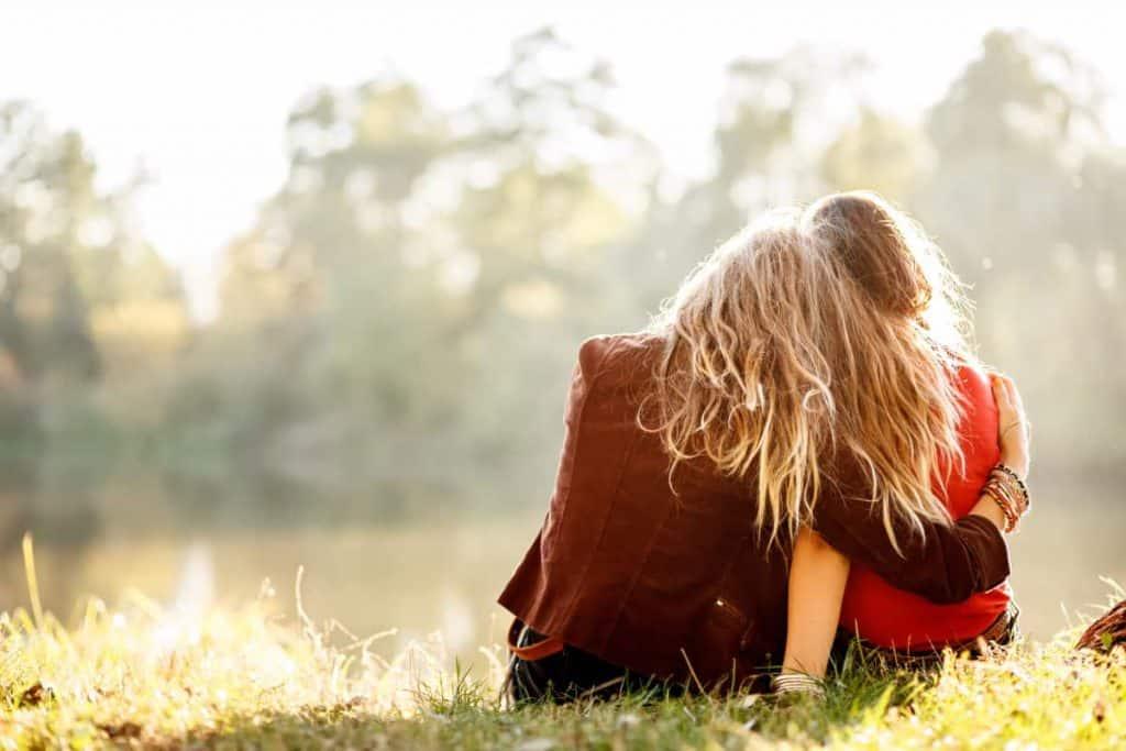 Two women with their backs to the camera sitting in grass with one with the arm around the other comforting her friend