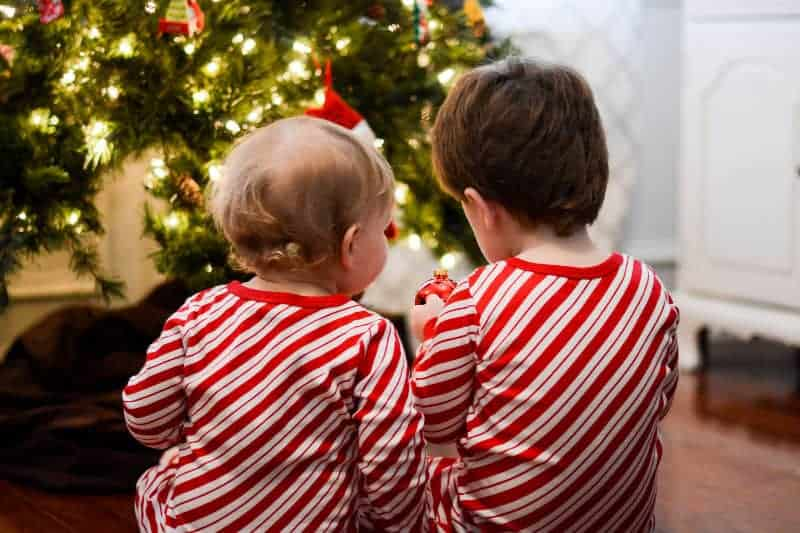 2 small boys in front of Christmas tree in candy cane pajamas
