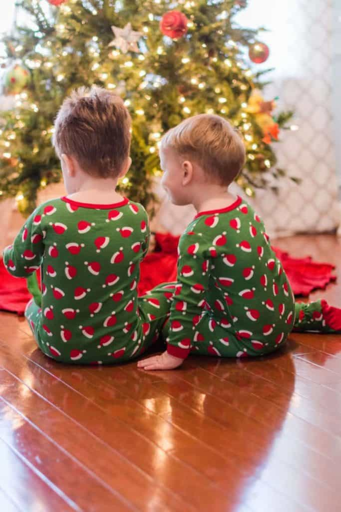 2 little boys in front of Christmas Tree in Santa Hat Pajamas