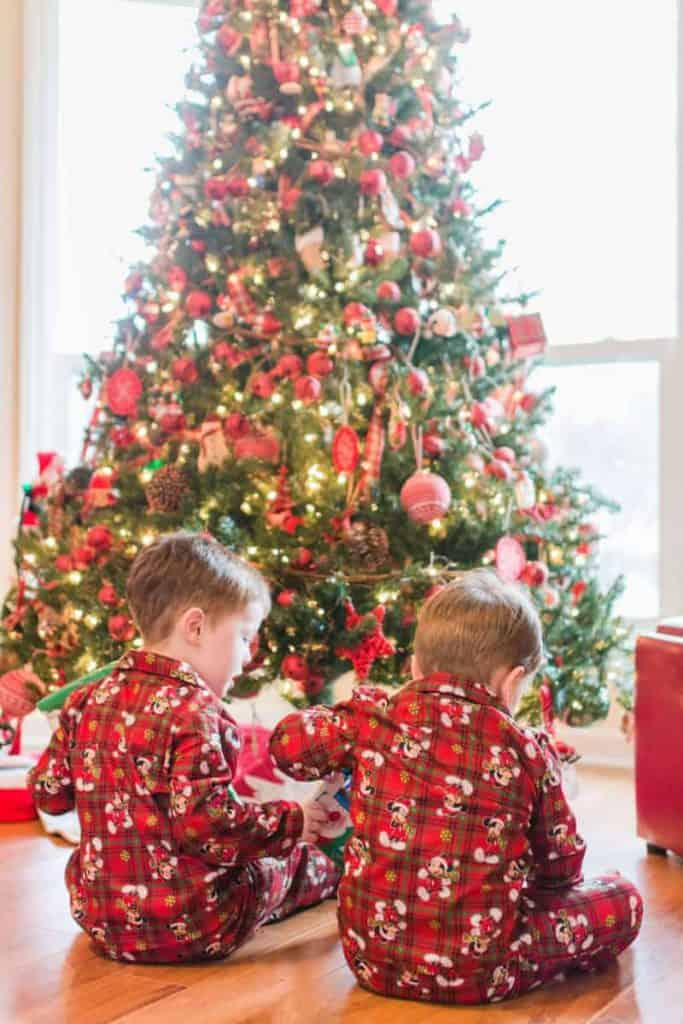 2 little boys in front of the Christmas Tree with plaid christmas pajamas