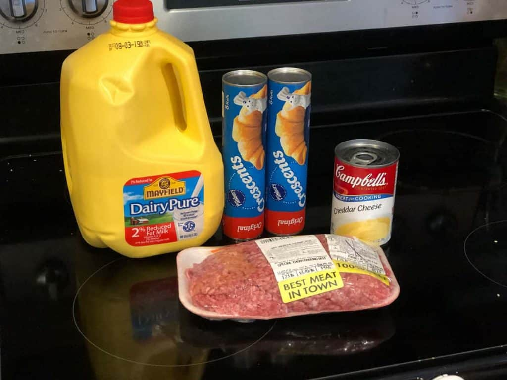 Ingredients for easy one-pot cheesy meat bake including milk, crescent rolls, ground beef and cheddar cheese soup