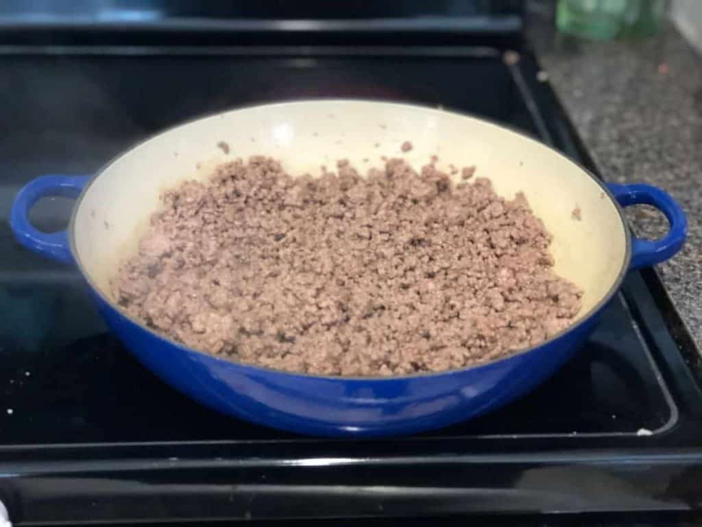 Ground beef being cooked from raw to fully cooked brown