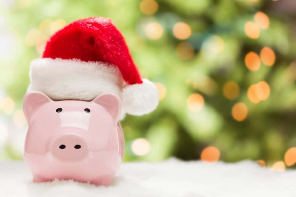 piggy bank with santa hat on, sitting in fake snow, with a lit Christmas tree in the background