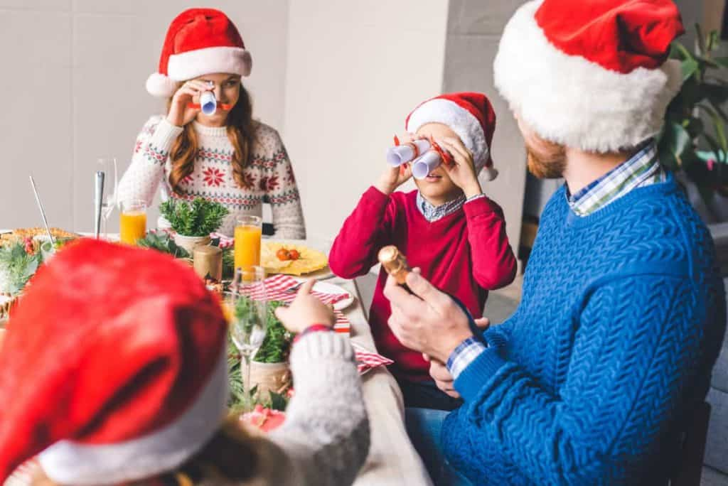 Family sitting at Christmas table with Santa hats playing together while eating