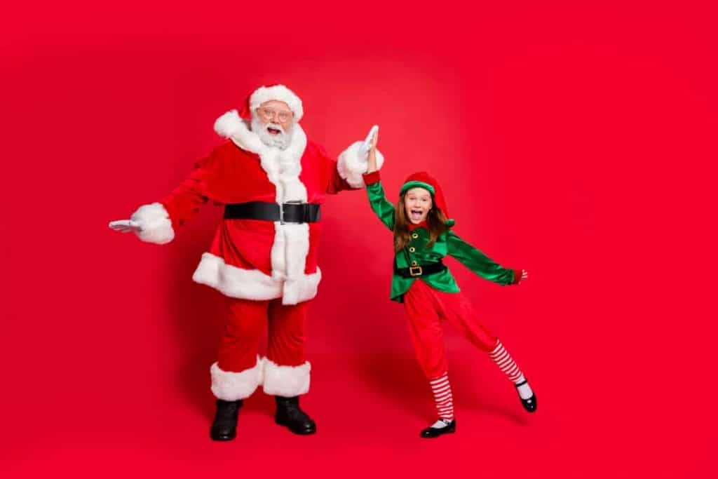 Little girl dressed in an elf outfit high-fiving Santa