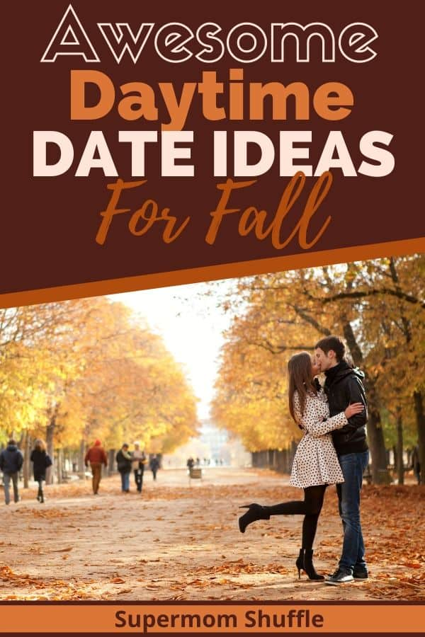 couple kissing in a park in the fall with leaves all around