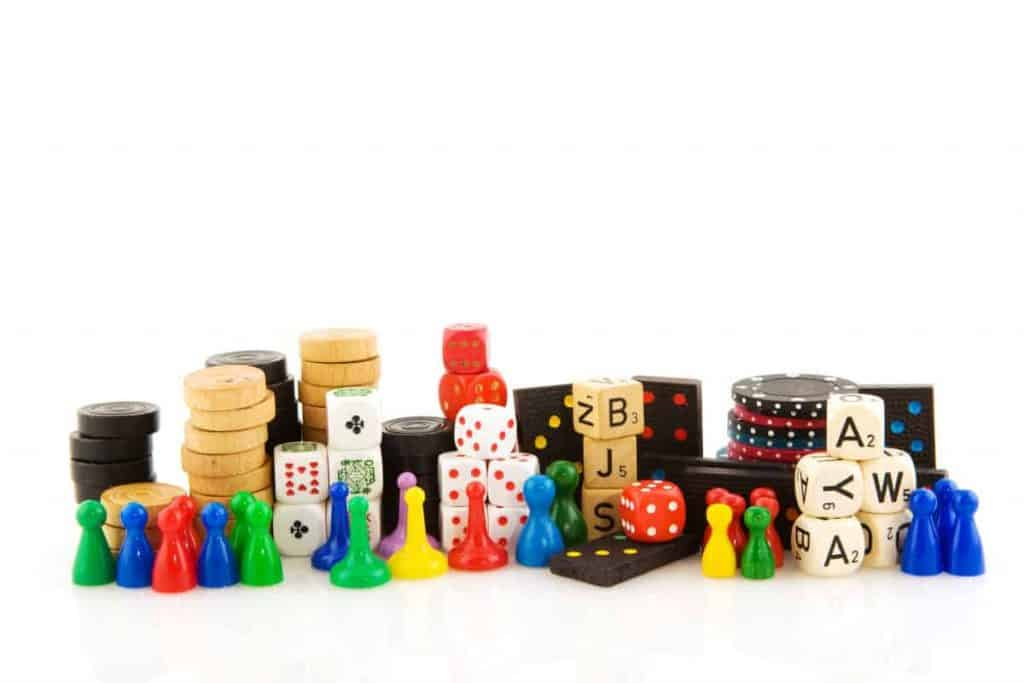 game pieces with dice, scrabble, poker chips, sorry tokens and boggle dice