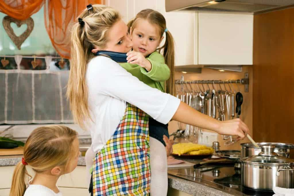 Busy mom cooking holding a child while on the phone with another child by her side