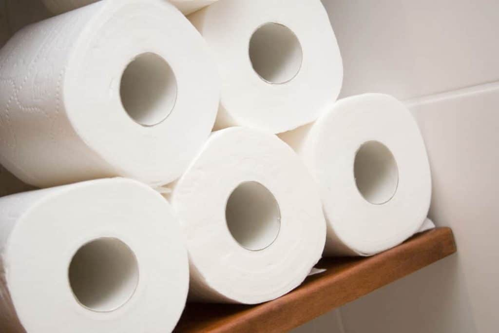 Toilet paper rolls stocked on a wooden shelf
