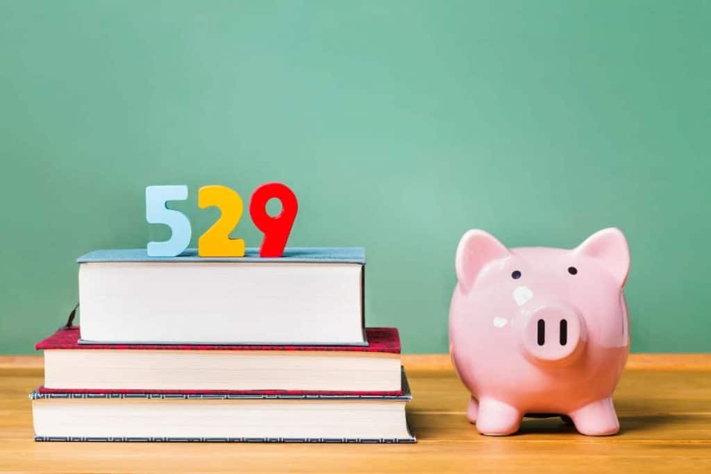 Piggy bank with a stack of books with the numbers 529 for college savings