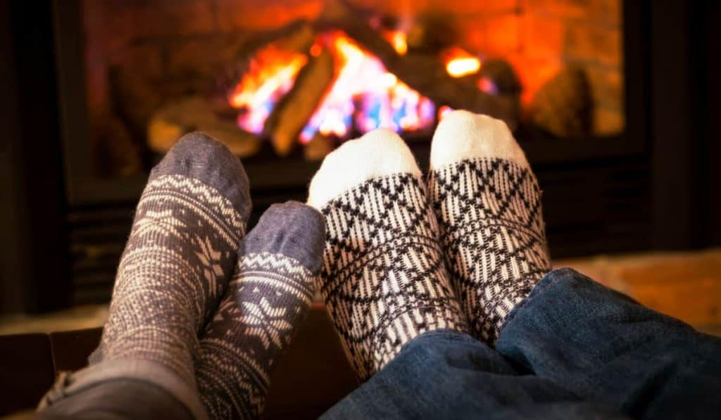 woman and man wearing socks with feet touching in front of the fireplace