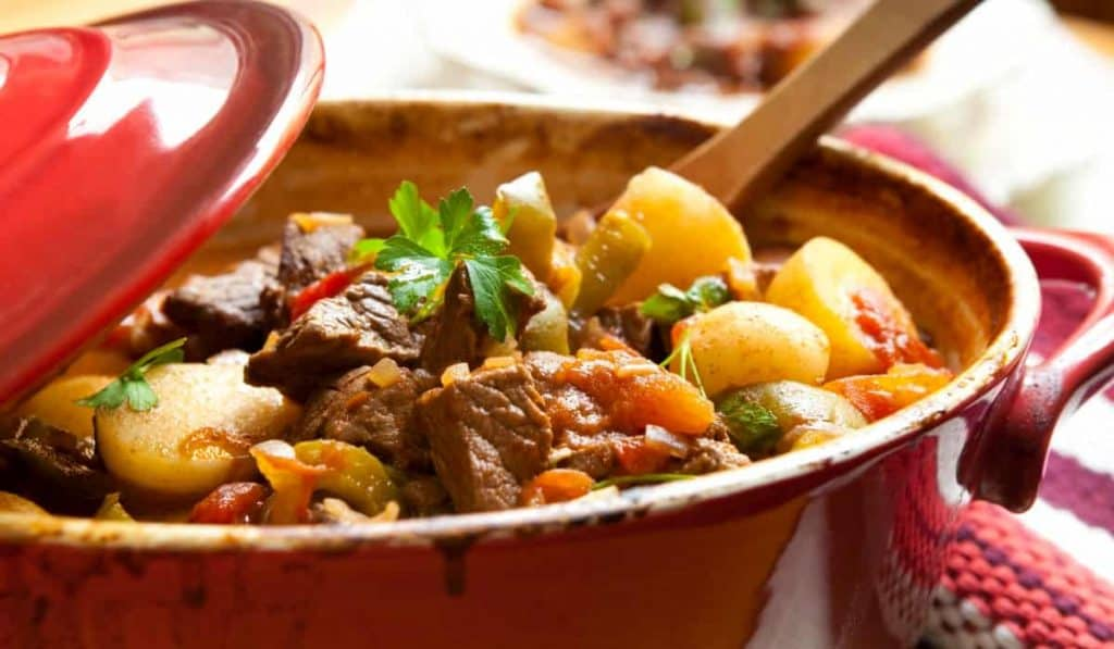 Cast Iron dutch oven full of beef stew with a wooden spoon