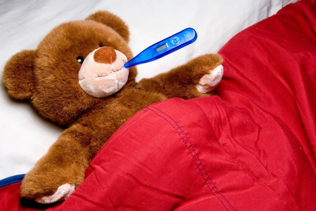 Teddy Bear under a red blanket with a blue thermometer checking for fever