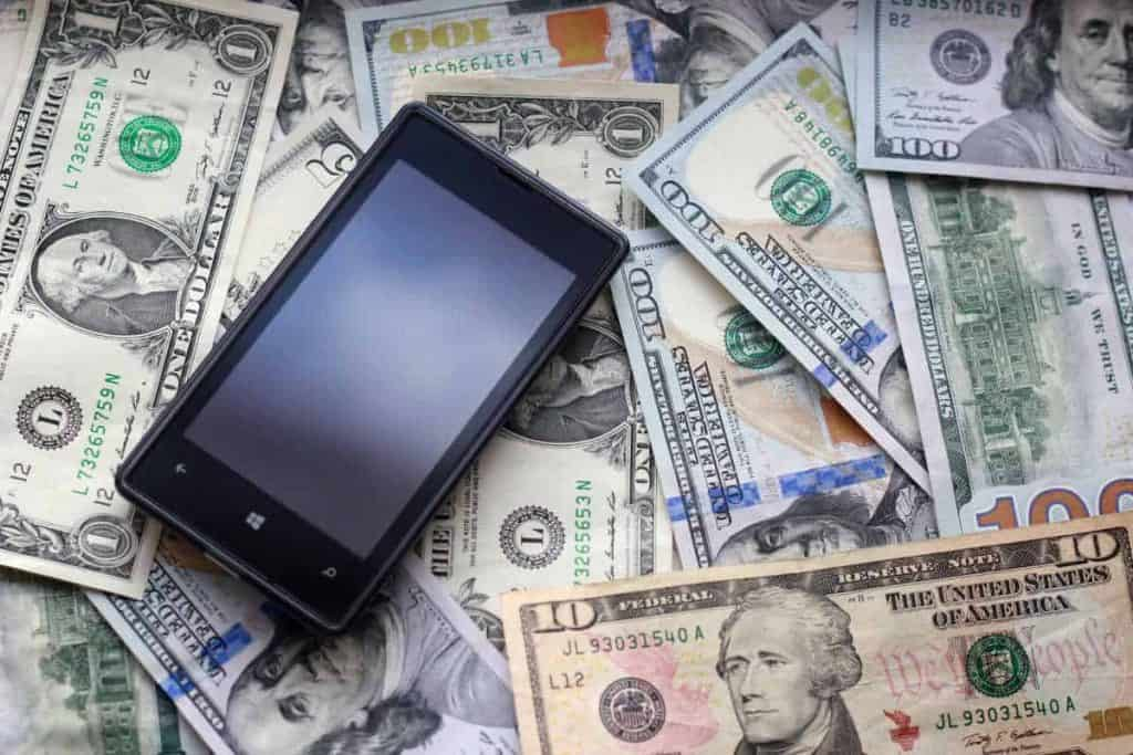 cell phone lying in pile of cash money