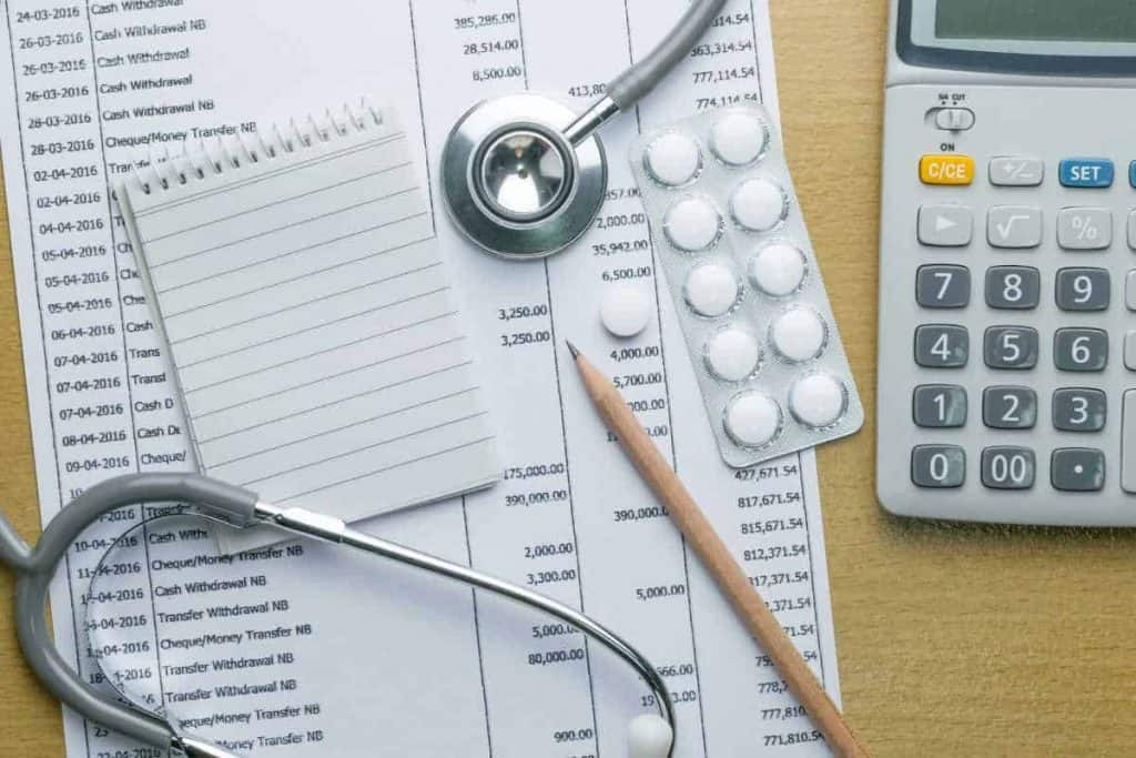 calculator with stethoscope and medical bills and medicines