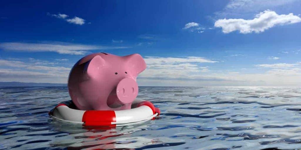piggy bank on life preserver in ocean