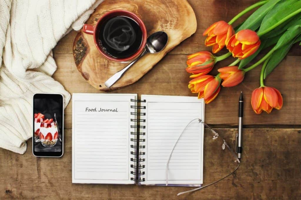 tulips, coffee, notepad, glasses, pen and phone for journling as part of a daily self-care care routine